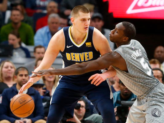 Denver Nuggets' Nikola Jokic, left, of Serbia, keeps the ball away from Minnesota Timberwolves' Gorgui Dieng during the first half of an NBA basketball game Wednesday, April 11, 2018, in Minneapolis. (AP Photo/Jim Mone)