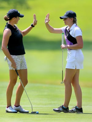 Tessa Teachman exchanges a high five with high school golfer Deanna Tinch, of Churchville-Chili, after Tinch made a putt during the Pro-Am in the Danielle Downey Classic at Brook-Lea on July 13, 2015.