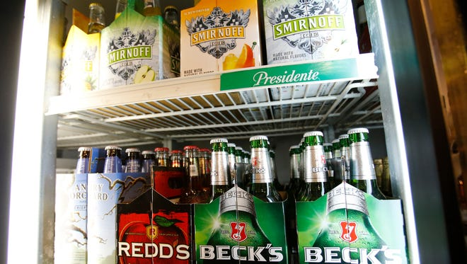 Six-packs of beer for sale are seen Oct. 19, 2015 at Sobe Liquors liquor store in South Beach in Miami Beach. Under current state law, grocery stores that sell beer and wine are prohibited from selling spirits in the same area. A proposed Senate bill could change that.