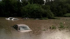 Cars are flooded in the backyards of homes along Vine