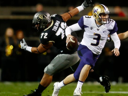 Washington quarterback Jake Browning, front, escapes