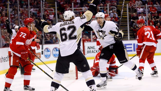 The Penguins' Eric Fehr (16) celebrates his third period goal with Carl Hagelin (62) as Red Wings forwards Andreas Athanasiou, left, and Tomas Tatar look on during Saturday's 7-2 loss at Joe Louis Arena.