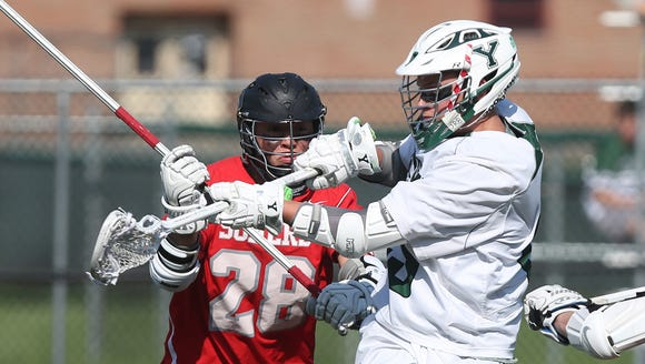 Yorktown's Alex DeBenedictis (43) fires a shot for a first half goal in front of Somers' Brian Marcus (28) during lacrosse playoff action at Yorktown High School May 23, 2018. Yorktown won the game 17-4.