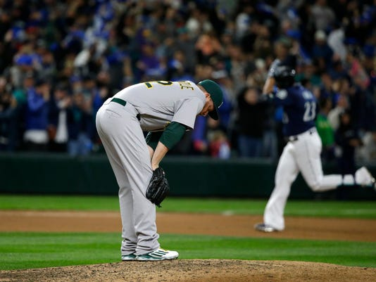 Oakland Athletics pitcher Sean Doolittle, left, reacts on the mound as Seattle Mariners' Nelson Cruz rounds the bases after hitting a two-run home run during the seventh inning of a baseball game, Saturday, Oct. 1, 2016, in Seattle. (AP Photo/Ted S. Warren)