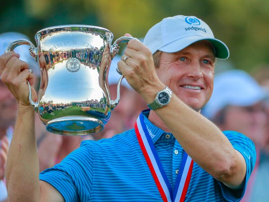 David Toms holds the trophy after winning the 2018
