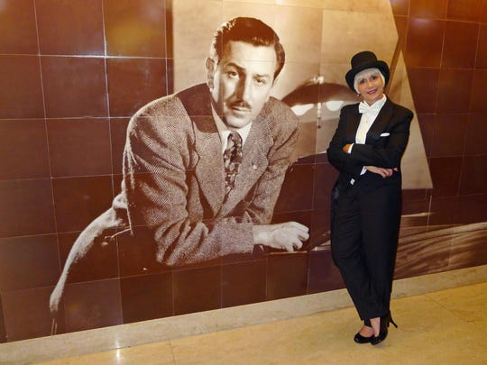 Joyce Wilden stands with a large mural of Walt Disney