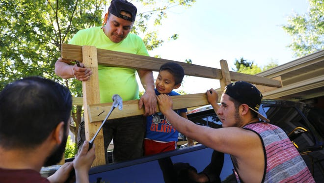 Miguel Hernandez, left, along with co-worker Pedro Tepole, center, and his cousin Eric Hernandez, build a structure on the back of Miguel's pickup truck on May 31, 2017, to help carry their belongings to Mexico. Thomas Hernandez, 5, watches the construction project. Hernandez and Tepole, along with three other dairy workers, left for Mexico the following morning.