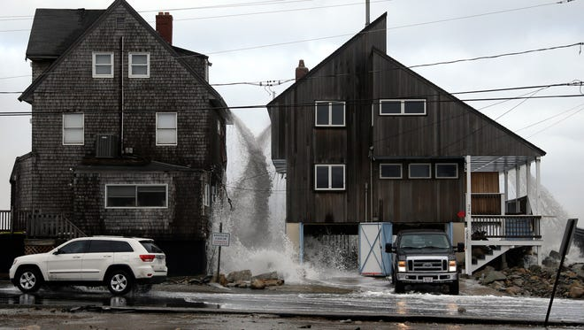 Ocean water pours off the roofs of these beachfront homes, Tuesday, March 6, 2018, as high surf continues in Marshfield, Mass.