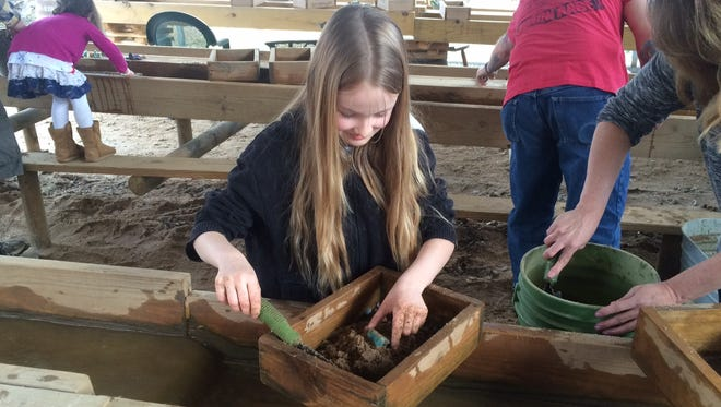 Tayler Moore, 9, and her mother, Fran Hanford, dig for gems at the Elijah Mountain Gem mine recently. The family is from Charleston, S.C.