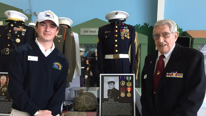 From left, Will Twomey and Korean War veteran Al de Vito flank de Vito's Marine Corps uniform, helmet, dog tags and other memorabilia he donated to Will for his uniform collection, which was recently on display at the Palm Springs Air Museum.