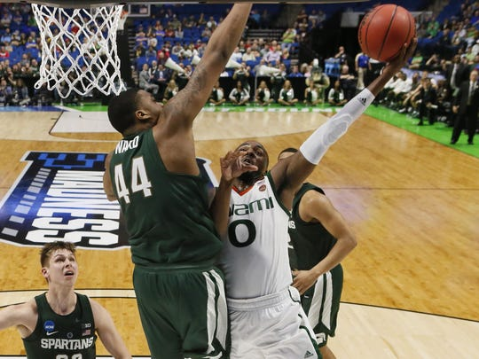 Miami's Ja'Quan Newton (0) shoots in front of Michigan State's Nick Ward (44) in the second half of a first-round game in the men's NCAA college basketball tournament in Tulsa, Okla., Friday, March 17, 2017. Michigan State won 78-58. (AP Photo/Sue Ogrocki)