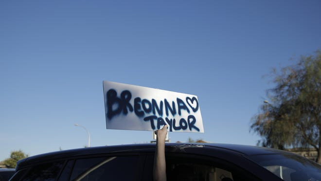 A person holds up a sign with the name of Breonna Taylor during a demonstration in Las Vegas on Friday, June 19, 2020, to mark Juneteenth, the holiday celebrating the day in 1865 that enslaved Black people in Galveston, Texas, learned they had been freed from bondage, more than two years after the Emancipation Proclamation.