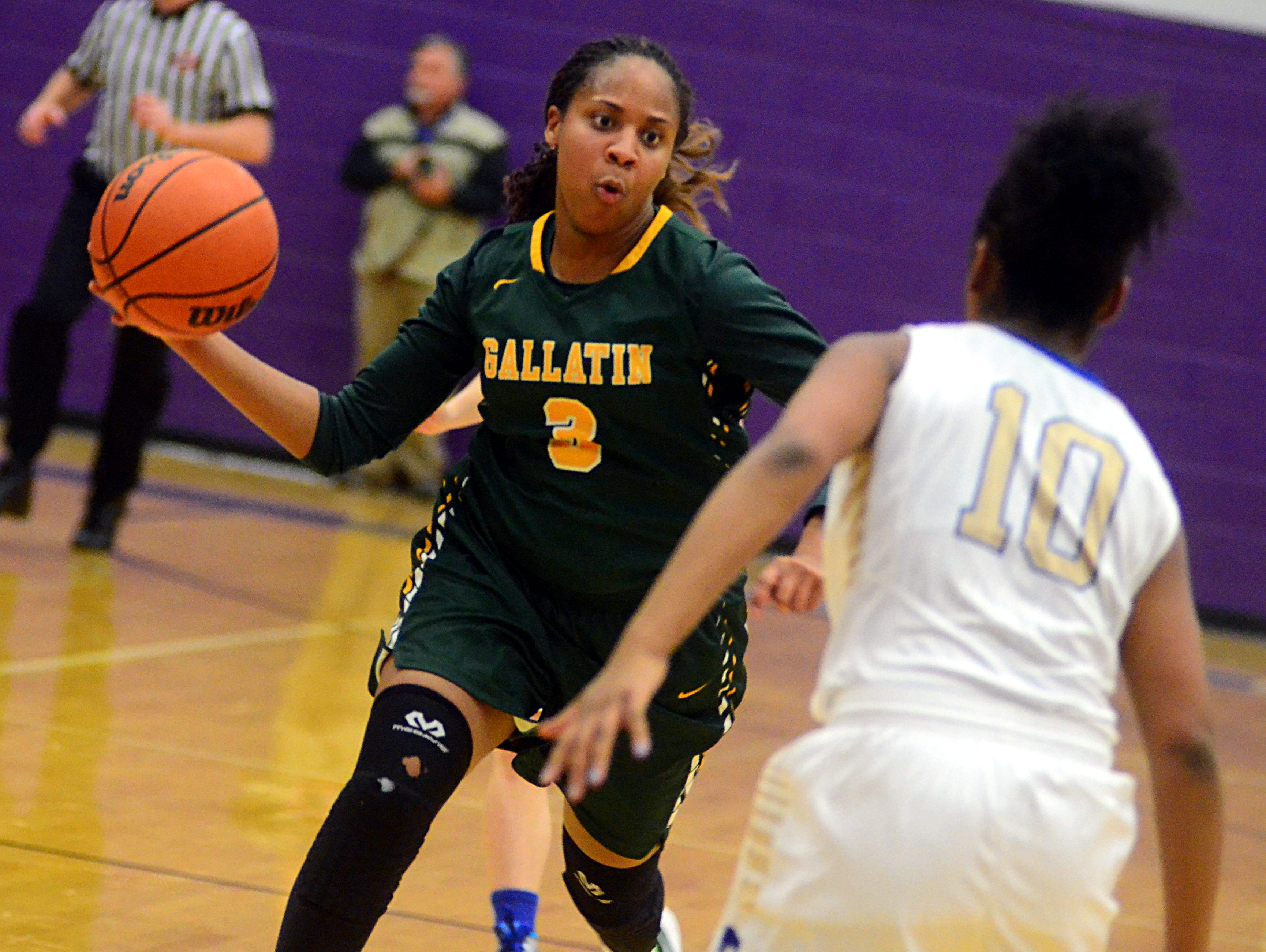 Gallatin High senior Rene Hudson throws a one-handed pass as Wilson Central sophomore Kenadhi Killebrew looks on during first-quarter action. Hudson scored 10 points.