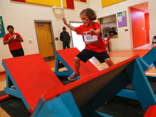 Stevie Fishburn, 6, races across an obstacle Friday during the Navajo Ninja Kids Competition at the Shiprock Youth Complex.