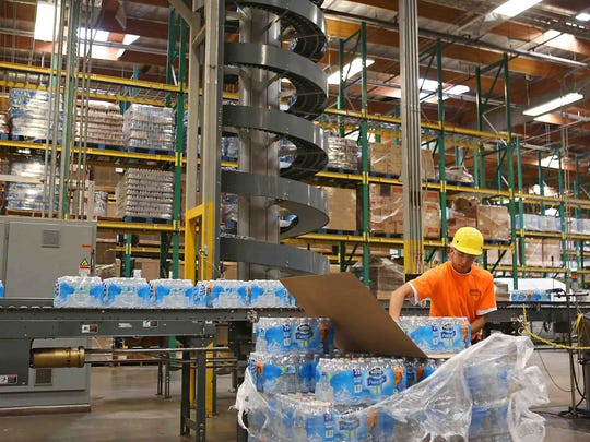 A worker packages bottled water at Nestle Waters North