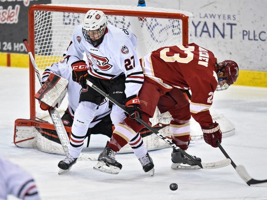 St. Cloud State's Dennis Cholowski and Matt Marcinew of Denver concentrate on the puck near the SCSU goal during the first period of the Friday, Jan. 20, game at the Herb Brooks National Hockey Center in St. Cloud.