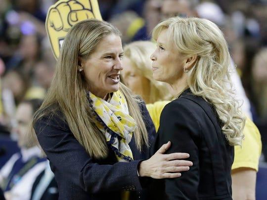 Michigan head coach Kim Barnes Arico, left, meets with Michigan State head coach Suzy Merchant before MSU's 86-68 win Feb. 19, 2017 in Ann Arbor.