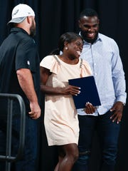 Middletown's Daija Lampkin receives the Female Athlete of the Year award from Eagles players Jon Dorenbos (left) and Wendell Smallwood during the Delawareonline Sports Awards at the Bob Carpenter Center Wednesday.