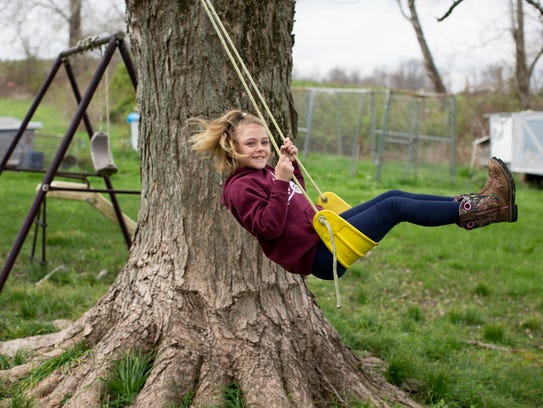 Bailey Price, 8, Eubank, Kentucky, plays on the swing her dad, Jerry 'Jed' Price, made her before his death two years ago from an overdose.