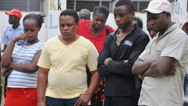Shocked members of the Maximum Revival Ministries Church view the body of their assistant pastor George Karidhimba Muriki outside the church after he was shot dead by armed gunmen on a motor bike as he was entering into the Church for a Sunday service in Mombasa, Kenya, Sunday Jan. 11, 2015.