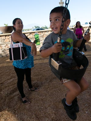 Diego Flores, 4, asks his mom Martha to push the swing seat during Rancho Las Flores Park's ribbon-cutting ceremony Saturday morning.