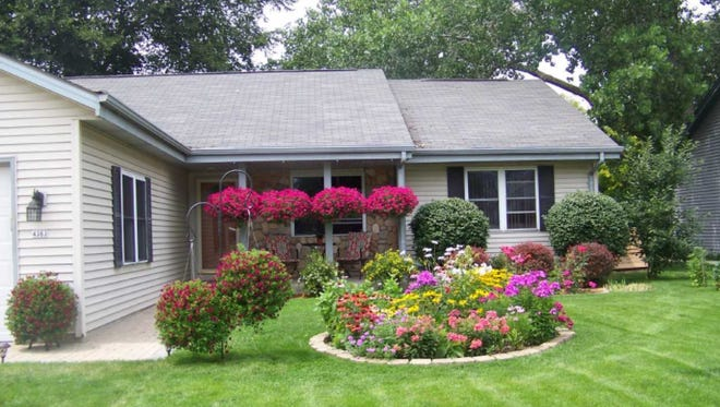 District 1: 4363 S. 50th St. Judges' comments: Drive to 4363 S/ 50th for an eye-opener. Property owners Mr. and Mrs. Bzdulw bring their gardening talents from Poland, using spectacularly huge red baskets of roses and currents and unusual bushes.