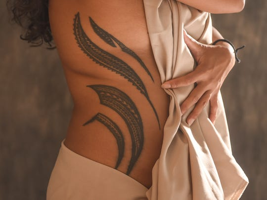 Elicia Santo Tomas displays a Samoan tribal tattoo she acquired during Festival of Pacific Arts Guam in 2016.