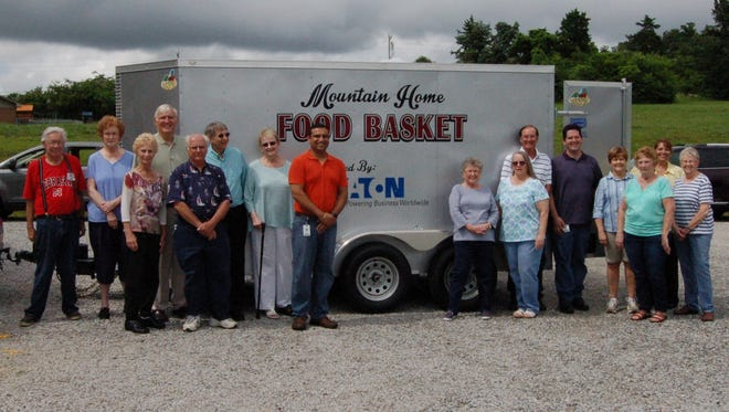 Eaton Corporation employees and Mountain Home Food Basket volunteers pose with the food pantry's new trailer. Eaton donated the money used to purchase the trailer.