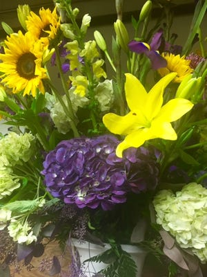 A large arrangement of fresh-cut flowers was created by Schroeder's Flowers designer Stephanie Kane in LSU Tigers colors of purple and gold for a private tailgate party Saturday for 550 fans from Louisiana. Kane said they specifically requested no red.