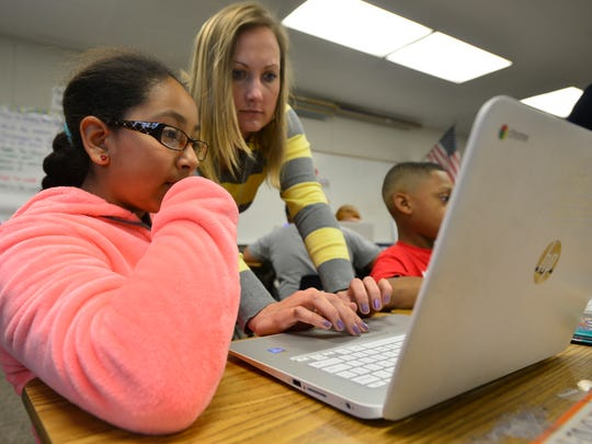 Jessica Wynn, a Highland Elementary fourth-grade teacher, works fractions with Dayana Cruz-Armenta, 10, on an HP Chromebook, which are used for Smarter Balanced testing.