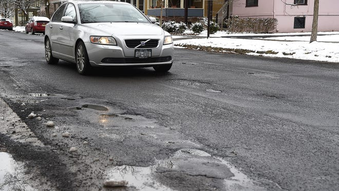 North Aurora St. in Ithaca's Fall Creek area is plagued with potholes, some of which have been patched.