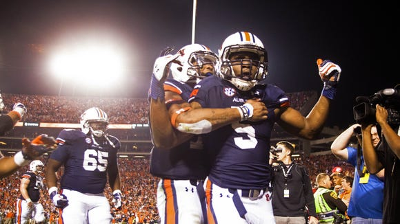 Auburn quarterback Nick Marshall (14) grabs wide receiver Ricardo Louis (5) after Louis scored the game-winning touchdown.