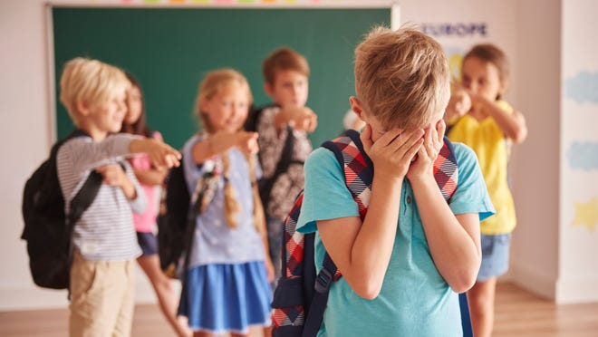 Picture showing children bullying child at school.