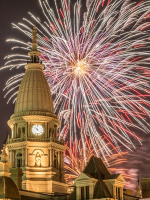 Tippecanoe County Courthouse lit up by fireworks.