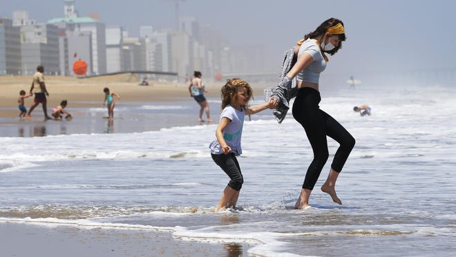 On May 22, 2020, Victoria Faughnan, right, and Evelyn Faughnan, play in the surf in Virginia Beach, Va., the day the state reopened the beachfront during the coronavirus pandemic. The pandemic not only upended the tourism industry, but how states, cities and attractions market themselves as summer travel destinations.