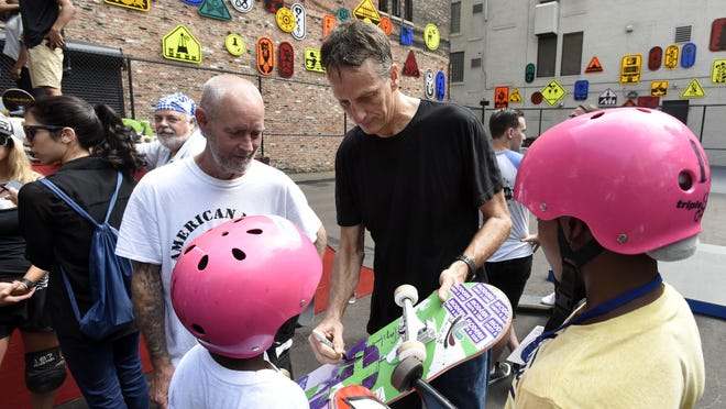 Professional skateboard legend Tony Hawk, center, signs an autograph for Rashad Wright, foreground-left, and his cousin, Daishon Nelson, right, both 11 and of Detroit, as Hawk stands with fellow pro-skater Bill Danforth, left.
