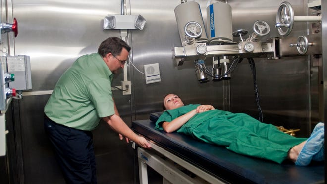 Chris Greene, left, and Adrianne Perry demonstrate the scanner used in the Lie Down and Be Counted program to provide free lung and whole body scans for people over the age of 13 who reside within a 100-mile radius of the WIPP site, now in its 20th year of operation.