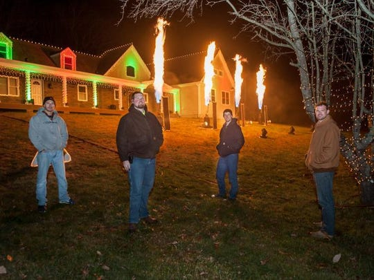 Wall Christmas Light Show organizers posing for a photo as the pyrotechnics erupt at a recent trial run. From left: Mike Roberti, Brian Brateris, Trevor Ferguson and Dan Brateris.