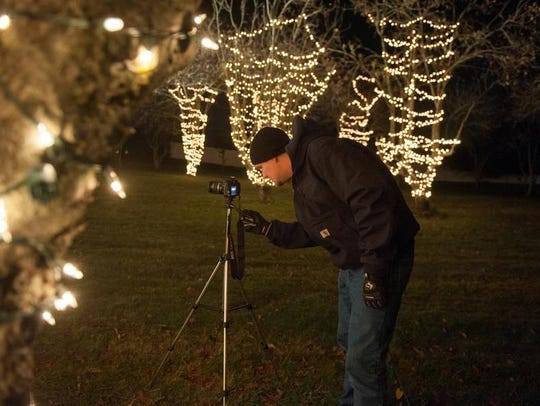 Brian Brateris checks some equipment during a trial run for the2015 Wall Christmas Light Show.