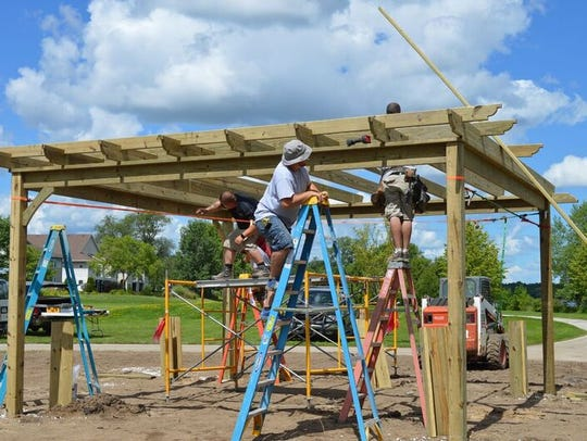 Volunteers build a pergola at Washington Park in Two