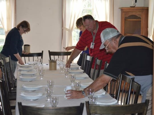 Setting the table in the Wade House dining room is one of the dinner preparation chores assigned to Hearthside Dinner participants. Hearthside Dinners will be offered on Saturdays, Feb. 18, March 18 and April 22.