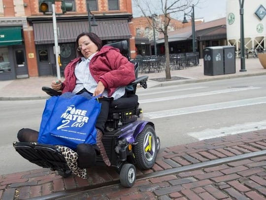 Vivian Armendariz steers an electric wheelchair around vehicles parked on Matthews Street while running errands in Old Town in this file photo. Armendariz, who died March 30, advocated for improved mobility for residents with disabilities.