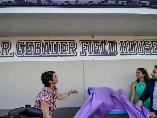 Legendary Old Bridge cross country and track coach Rich Gebauer's wife, son and daughter- in-law unveil the new sign named after him on the athletics field house during a ceremony on Friday at Lombardi Field in Old Bridge.