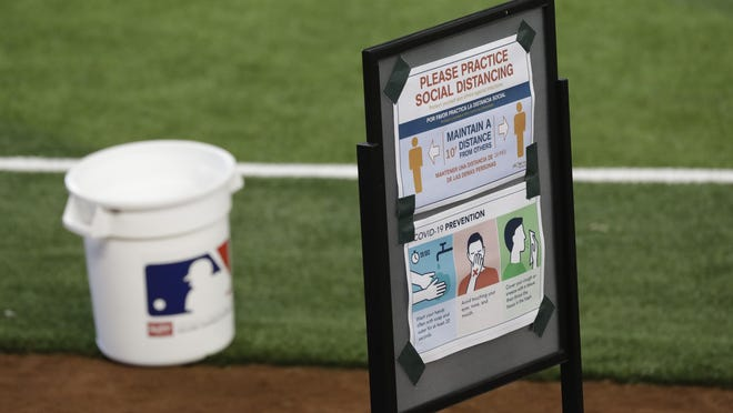 Signs stressing prevention against the new coronavirus are posted next to the field during a workout by the Miami Marlins at Marlins Park on Saturday in Miami.