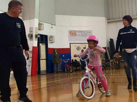 """Master Corporal Brian Whitte, left, and Sgt. Andrea Janvier, right, help guide Angelina Wise, 6, on her bike as part of the Wilmington Police Athletic League's """"How to Ride a Bike"""" program."""