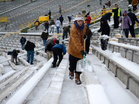Sammy Lett, of De Pere, shovels snow at Lambeau Field