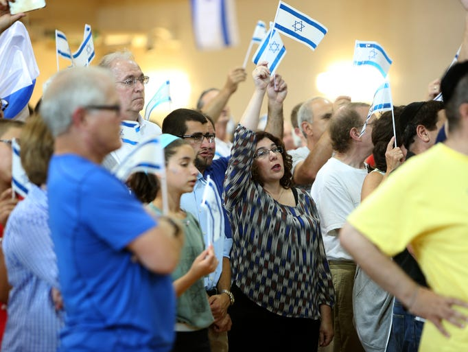 Supporters wave the Israeli flag during the Cincinnati Stands with Israel rally at the Mayerson JCC, in Amberley Village, on Sunday afternoon.
