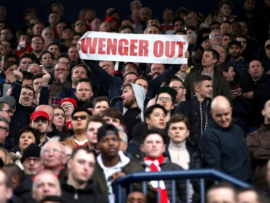 A fan holds up a banner, during the English Premier League soccer match between West Bromwich Albion and Arsenal,  at The Hawthorns, in West Bromwich, England, Saturday March 18, 2017.  (Nick Potts/PA via AP)