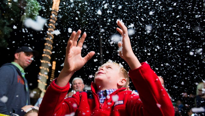 """Will Kramer, 9, looks up toward the """"snow"""" during the annual Christmas on Third celebration in downtown Naples on Monday, Nov. 21, 2016. The event featured tree lighting, ice sculptures, music and fake snow."""