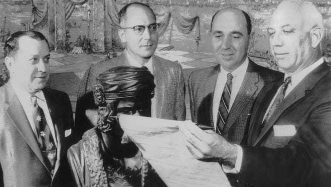 Lou Chiozza (right), president of the Italian Society, reads a Columbus Day proclamation from Gov. Frank Clement to fellow officers on October 13, 1955, during the annual Columbus Day banquet at the Catholic Club. Gathered around a bust of Columbus were (from left) Louis C. Pierantoni, society treasurer; Ralph M. Gagliano, secretary, and Leonard D. Pierotti, vice president.